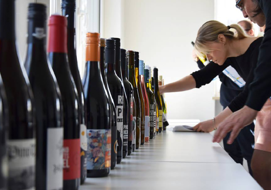 a line up of wine bottles with inspectors looking at the labels